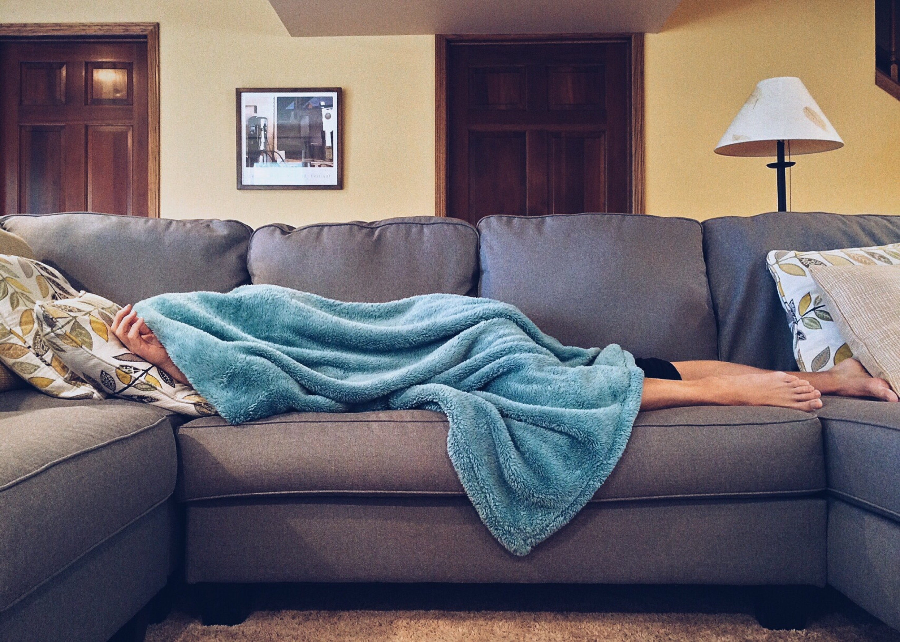 sick person laying on couch