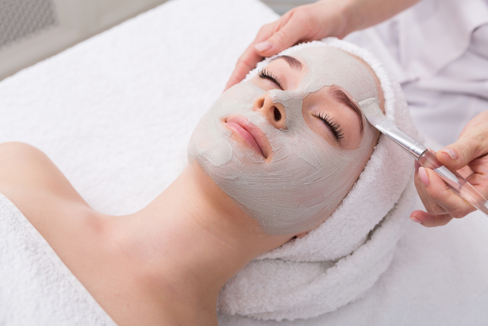 woman getting facial from a skincare professional