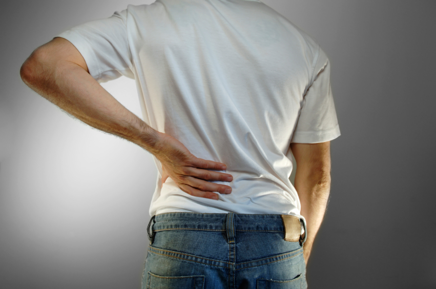 man in white shirt and blue jeans with hand on back, back pain