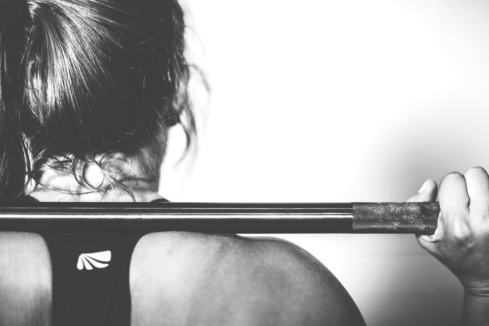 greyscale image of woman lifting barbell